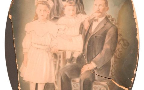 Damaged oval family portrait before photo restoration.